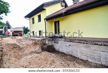 Rebuilding house digging dirt excavator stock photo for Digging foundation for house