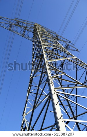 A big pylon which grows in the blue sky on a sunny day / subject / high voltage