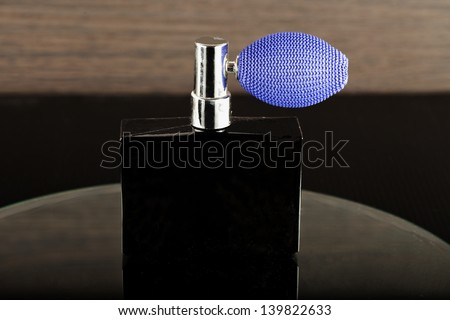 A black bottle of scent over a mirror