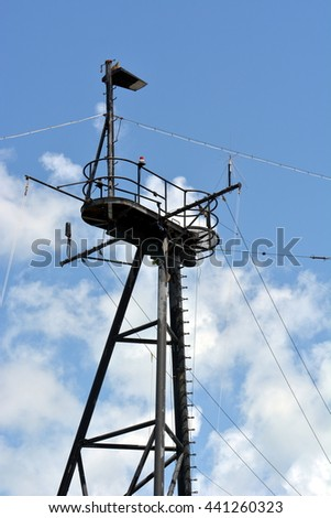 A black crow's nest tower on a ship against blue sky with clouds,