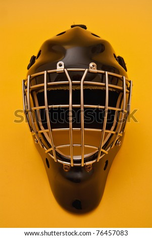 a black hockey goalie helmet on a gold background.  some scratches and wear can be seen on the helmet as it has been used.