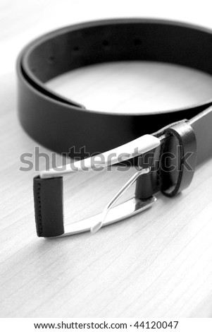 A black leather belt on a wooden surface