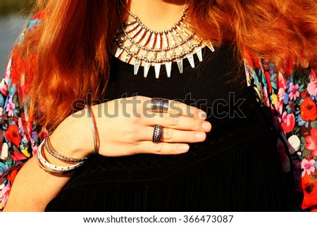 a black suede bag with fringe hands with bracelets and rings. Boho chic style, gypsy, hippie, bohemian