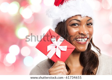 A black woman celebrating christmas holding a gift box