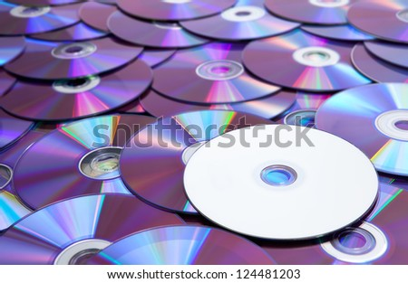 A blank and unlabeld DVD atop a pile of scattered DVDs.