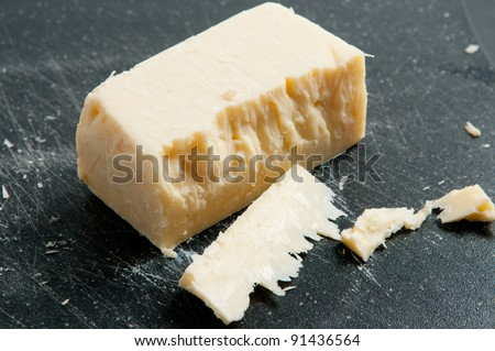 sharp white cheddar. a block of sharp white cheddar cheese, some cut in front on background h