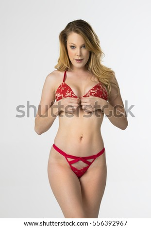 A blonde model poses in lingerie in a studio environment