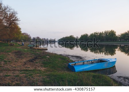 a blue boat moored to the banks of the river