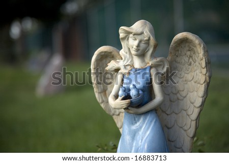 A blue glazed angel protects the garden and those she watches over.