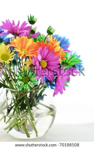 a bouquet of bright colored daisies in a vase, vertical with high key white background