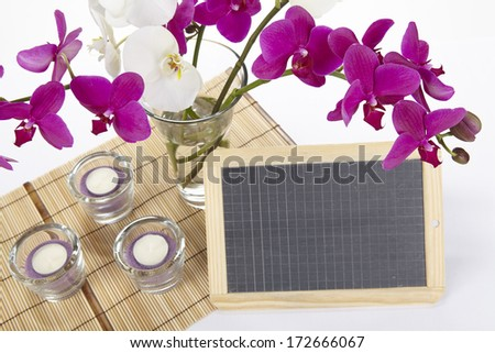 A bouquet of white and purple orchids into a vase standing on a place mat of bamboo. A little slate can be used as a free text field.