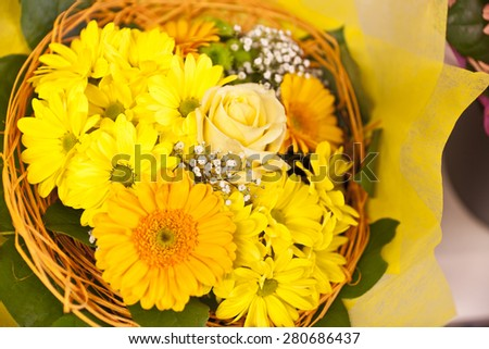 a bouquet of yellow and orange gerbera in basket