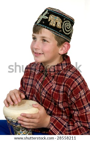 A boy  in the national hat , plays on the Bedouin drum tarbuka