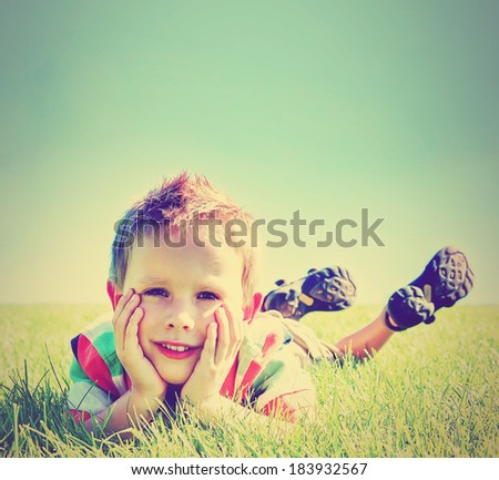 a boy laying in the grass against a blue sky done with a retro vintage instagram filter