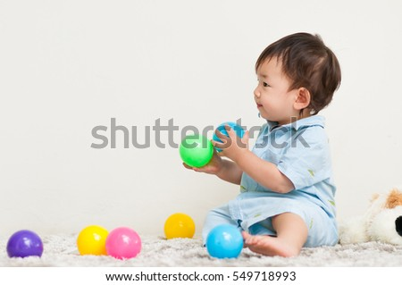 A boy playing colorful balls.