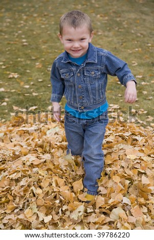 A boy running through the leaves in the fall.
