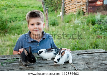 A boy with a rabbit in the garden