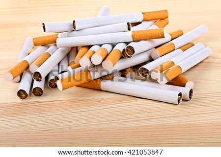 a bunch of cigarettes with orange filters on a wooden table