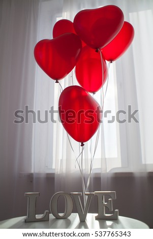 a bunch of red and white balloons above a white table with wood letters of word LOVE