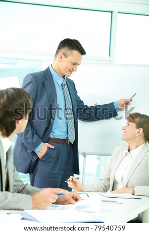 A business man showing something on a whiteboard and looking at colleague