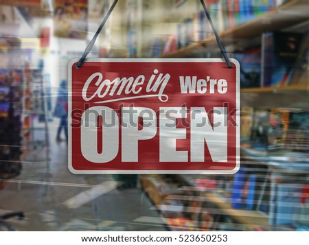 A business sign that says 'Come in We're Open' on a book store window.