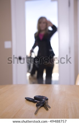 A business woman who is locked out of her house,  looking in through her door in her kitchen at her home and car keys she left on the table.