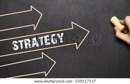 A businessman is drawing strategy concept with arrows on blackboard