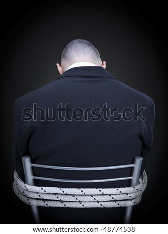A businessman is tied up on a chair turning his back to the camera.