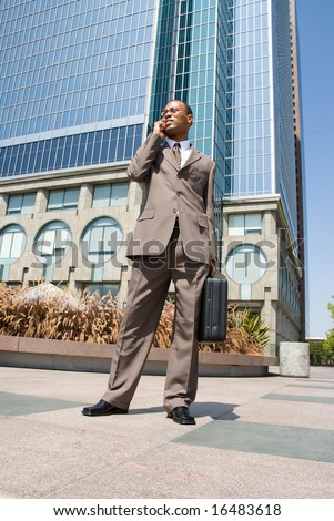 A businessman walks through a business park talking on his cell phone.