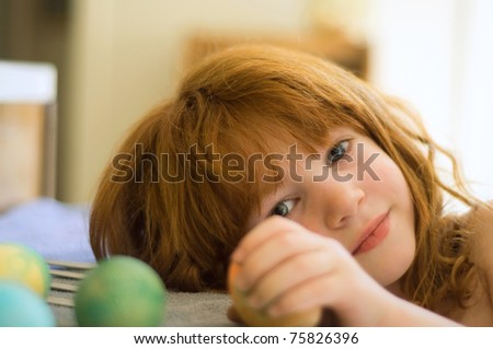 A candid shot of a four year old little girl with red hair holding her Easter egg