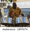 A caribbean musician playing steel drums with the ocean in the background. - stock photo