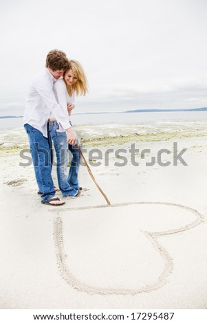 A caucasian couple in love drawing a heart sign on the beach