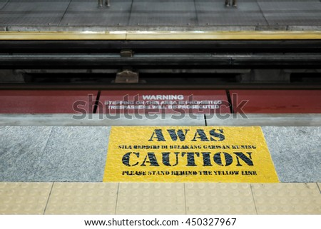 A caution signage in English and Malay language, informing passenger to stand behind the yellow line, on a train platform.