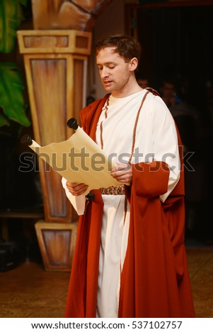 A character dressed in Roman costume reads from a scroll