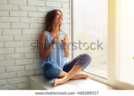 A charming young girl is dreaming about something while sitting on the window-sill. She is inspired by lovely sun and sun rays with lighten up the room