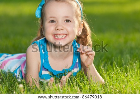 A cheerful pretty little girl is lying on the green grass