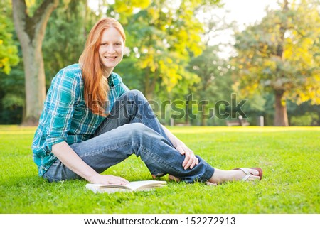 A cheerful young woman sitting a park with a book and smiling at the camera.