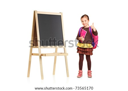 A child next to an empty school board holding book and showing thumb up isolated against white background