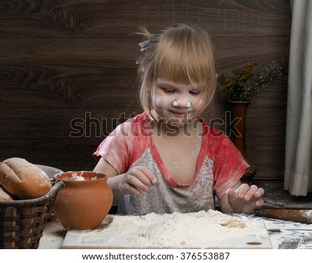 A child plays with the flour. Girl knead the dough. Girl funny stained with flour. Very fun game girl happy