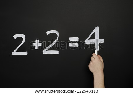 A child's hand drawing 2+2=4 in chalk on a blackboard