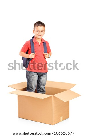 A child with backpack standing in a cardbox isolated on white background