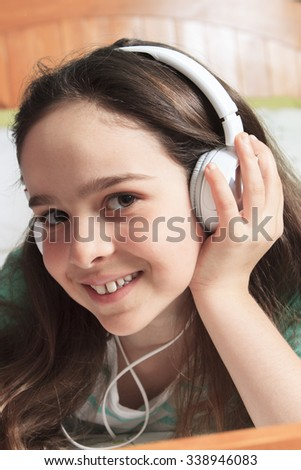 A children girl listening music lay on his bed