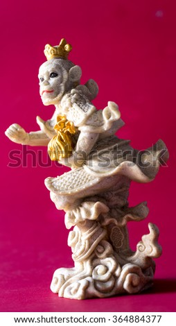 A chinese new year's ceramic figure represent a year of monkey holding gold ingot represent long live, prosper and good luck. Slightly de-focused and close-up shot. Copy space.