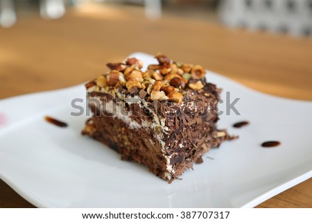A chocolate pie with caramel syrup and nuts (cake)