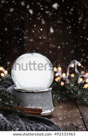 A Christmas rustic image of an empty snow globe with pine branches, cinnamon sticks and a warm gray scarf with gently falling snow flakes. Shallow depth of field with selective focus on snowglobe.