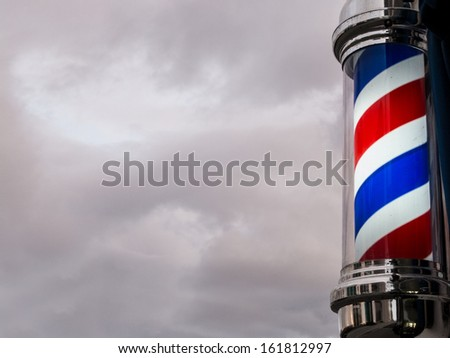classic barber pole set against a clouded sky background that is ...