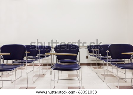 A clean Classroom Full of Blue Chairs