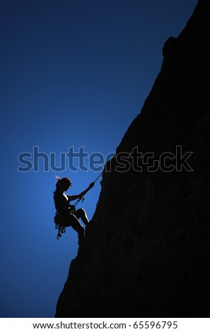 A climber hangs from a thread on the side of a cliff.