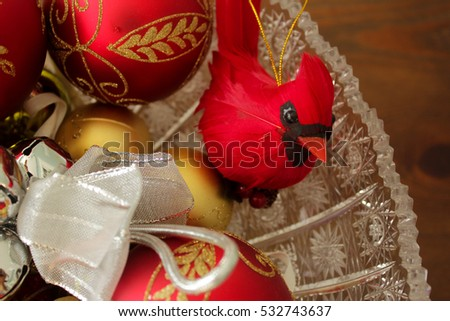 A close photo of a realistic cardinal decoration and decorative Christmas balls in a crystal bowl.