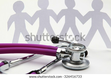 A close-up of a stethoscope and paper people, isolated on white